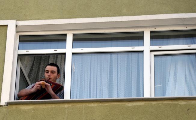 Evinin penceresinden çaldığı tulumla komşularına moral veriyor