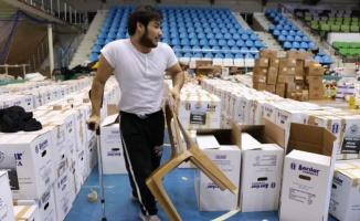 Koltuk değneğini bir yana bırakıp depremzedelere yüreğiyle yardım ediyor